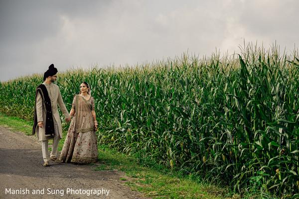 Indian couple walking by a corn field