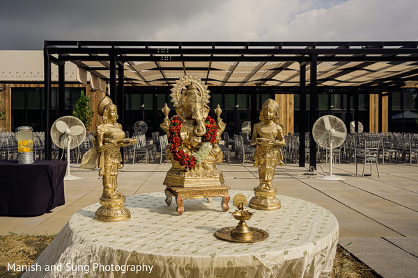 A table with a golden statue of Ganesha and two other figures