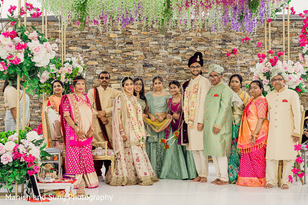 Indian couple and their Indian relatives posing on the wedding stage