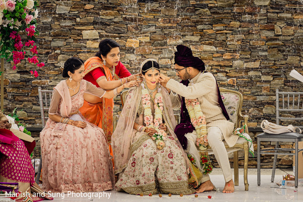 Indian groom and Indian relatives adjusting Maharani's hairdo