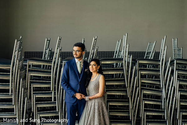Indian newlyweds posing in front of several stacks of chairs