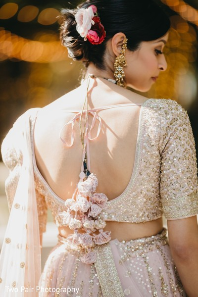 Indian bride showing her open shirt lehenga from backwards.
