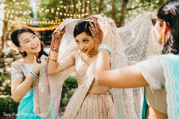 Indian bride getting her ghoonghat veil on.