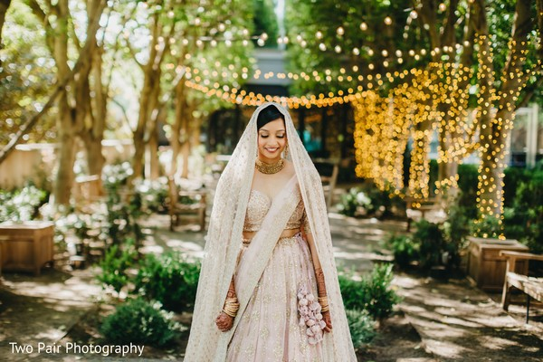 Indian bride wearing her ceremony lehenga with ghoonghat.