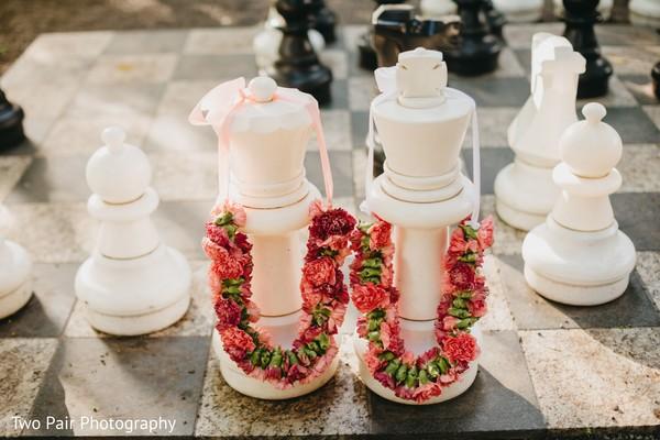 Indian wedding garlands capture on big chess decoration.