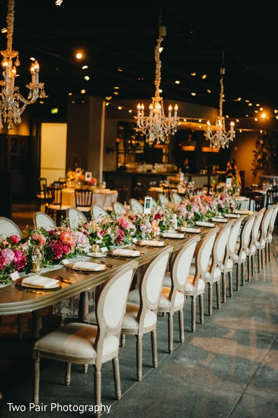 Long Indian wedding table chandeliers and flowers decor.