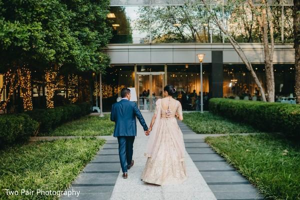 Indian couple walking into wedding reception.