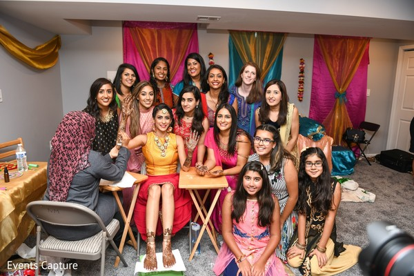 Indian bride with bridesmaids and flowergirls at mehndi party.