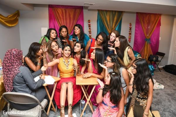 Indian bride posing at mehndi party with bridesmaids.