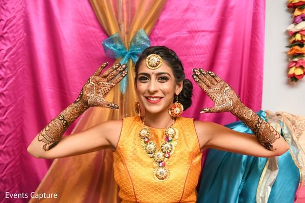 Indian bride showing her hands with mehndi art.