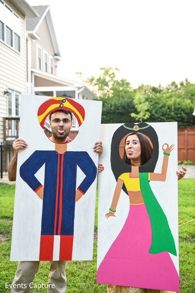 Indian couple posing with Face-in-the-hole boards.