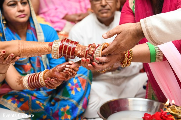 Closeup capture of maharani's red and golden bangles.