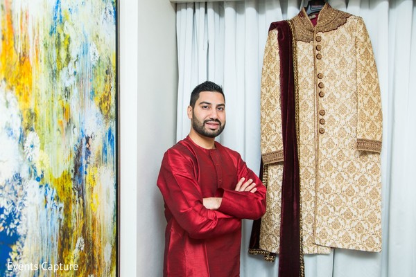 Indian groom next to his ivory and golden sherwani.
