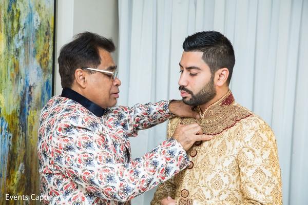 Indian groom getting his wedding ceremony sherwani on.
