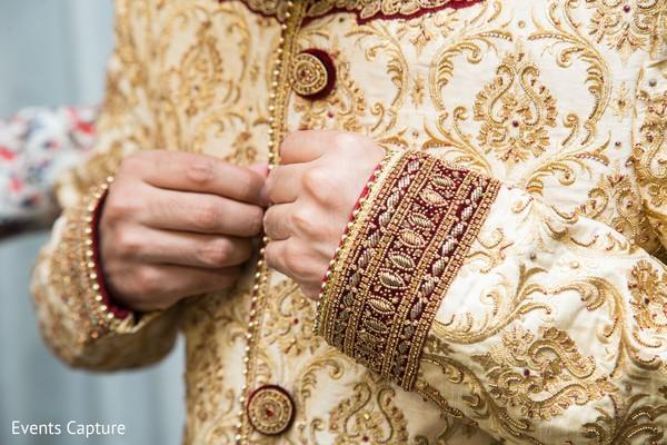 Closeup capture of Indian groom's sherwani embroidery.
