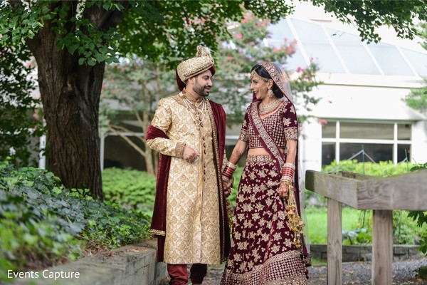 Indian couple posing outdoor on traditional ceremony outfits.