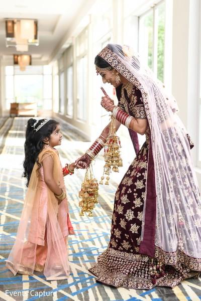 Indian bride on her ceremony lehenga talking to flower girl.