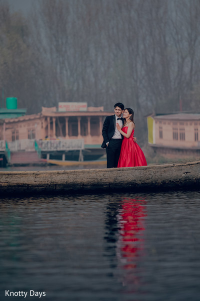 Indian couple standing on a boat on a lake.