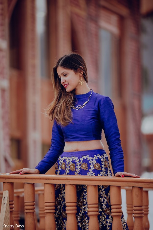 Indian bride on her royal blue openshirt lehenga.