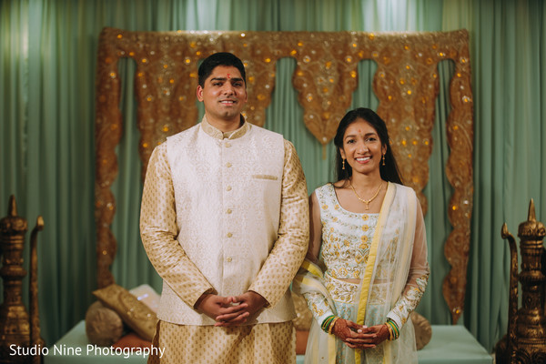 Indian couple standing in front of a stage