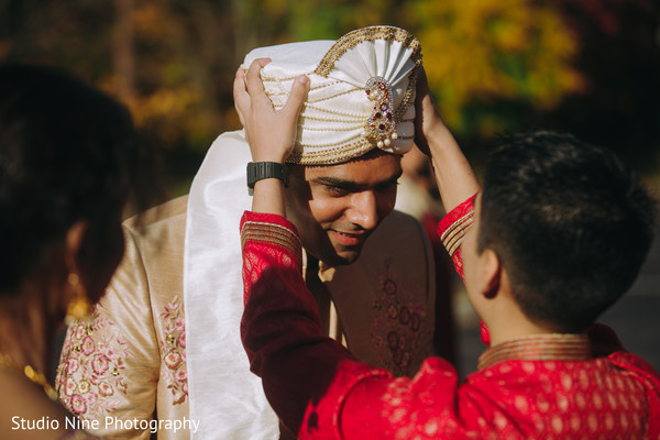 Indian relative putting a turban on the Indian groom