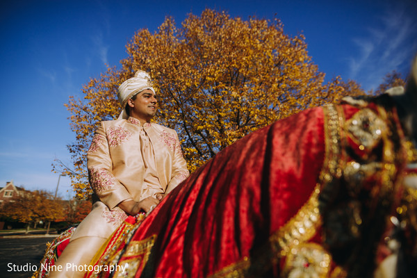 Indian groom riding a white mare