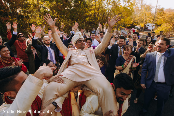 Indian groom being carried by his Indian groomsmen