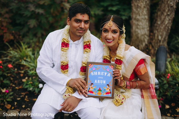 Indian newlyweds holding a framed drawing
