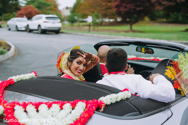 Indian newlyweds leaving in a sporst car