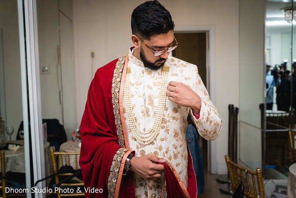 Indian groom adjusting his attire