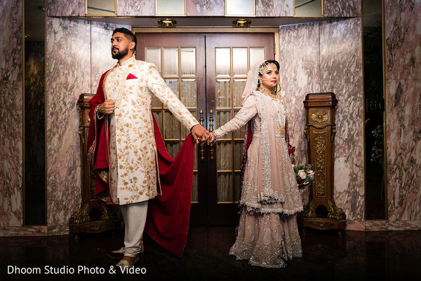 Indian couple, in their wedding attires, holding hands
