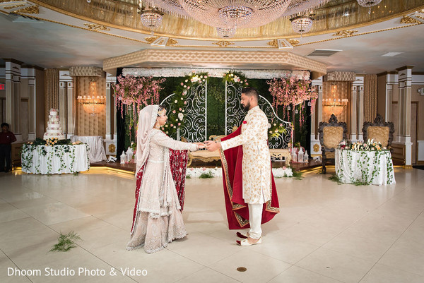 Indian newlyweds holding hands in the center of the dance-floor