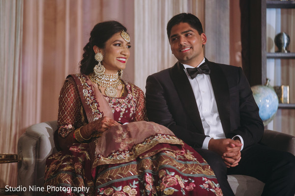 Indian newlywed couple sitting on stage