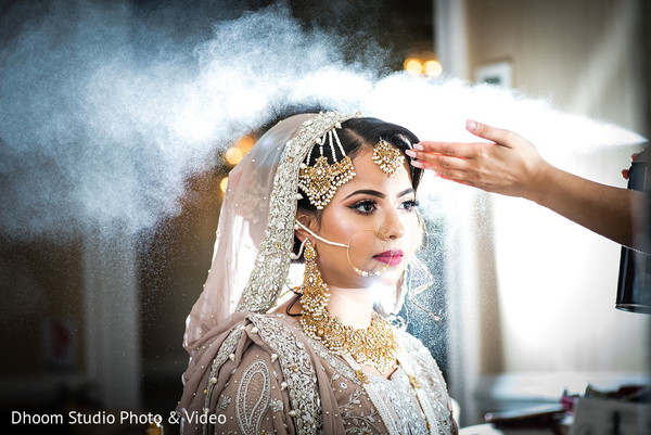 Hairspray being applied to the Indian bride