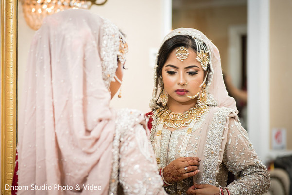 Indian bride looking at her attire in the mirror