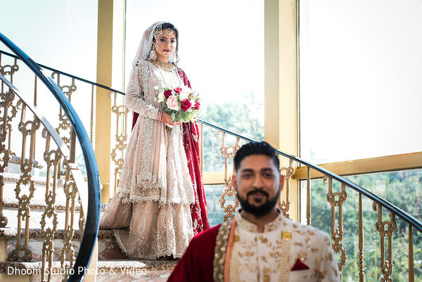 Indian bride coming down the stairs while the Indian groom waits