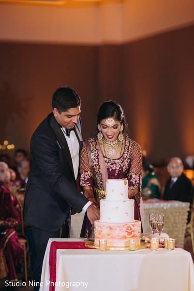 Indian newlyweds cutting the cake