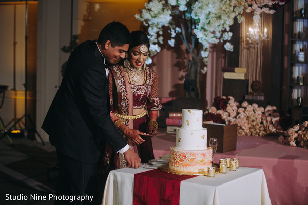 Indian newlyweds about to cut the cake