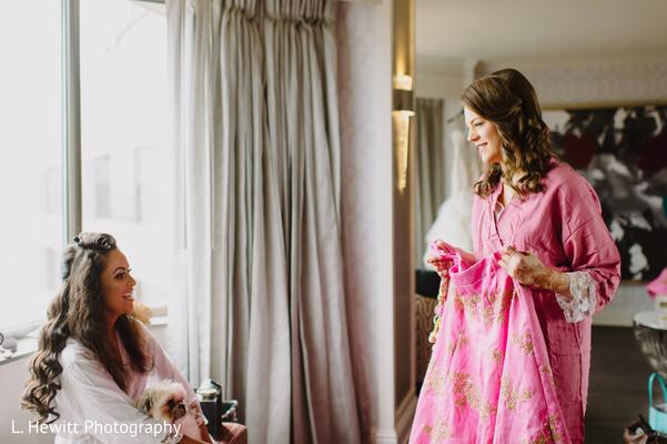 Maharani with bridesmaids looking at pink lehenga skirt.
