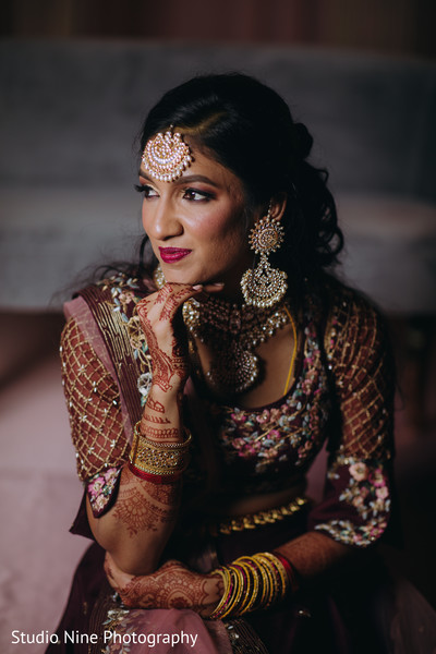 Indian bride in a dark red anarkali prior to the reception