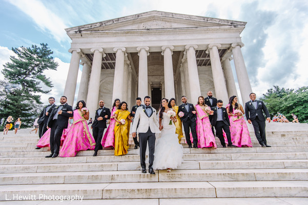 Indian couple walking down the stairs with bridesmaids and groomsmen.