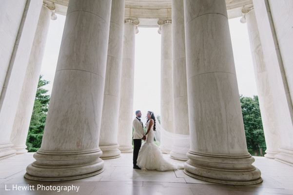 Indian couple posing in between big white columns.