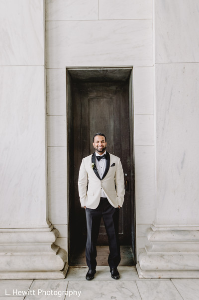 Elegant indian groom on his white and black wedding suit.