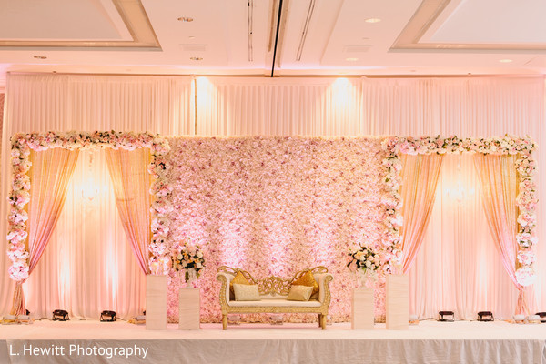 Indian wedding reception pink flowers and draping stage decor.