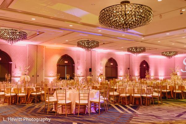 Indian wedding reception venue pink lights decoration.