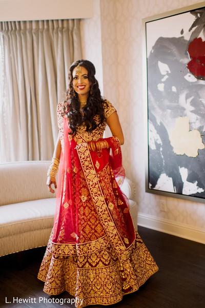 Indian bride wearing her golden and red wedding lehenga.