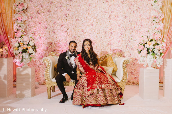 Indian bride and groom posing at wedding reception stage.