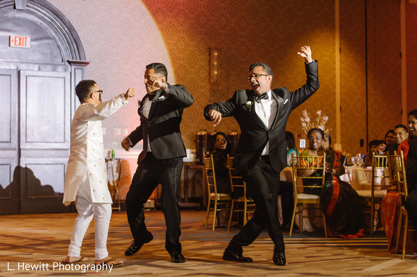 Indian groomsmen dancing at reception party.