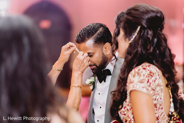 Indian groom getting a mark on forehead.
