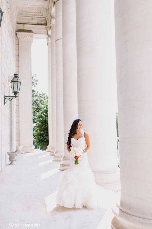 Indian bride posing on her white wedding dress.